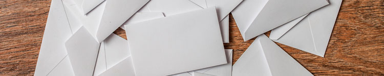 Custom Envelope Printing, Kenwel Printers Inc., Envelopes Scatterd on Wood Grain Background
